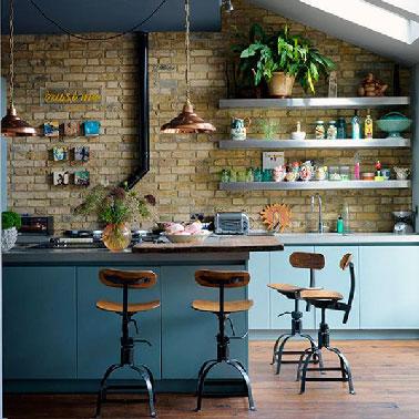 """Ambiance loft américain pour cette cuisine pimentée par des couleurs """"nature"""" : bleu, vert, jaune,une gammeparfaite sur un mur en pierre apparente plein de cachet."""
