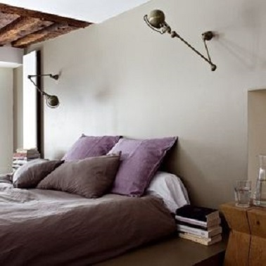 La couleur taupe du mur de cette chambre est relevée par la teinte parme des draps.  L'ensemble donne une chambre à la déco très tendance et une ambiance sereine.