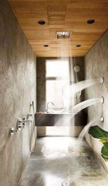 La salle de bain s'offre un spa à domicile avec cette douche à italienne et ces jets muraux et sa pomme incorporée au plafond en bois. Un appel irrésistible à la relaxation et à la détente absolue. L'enduit ciré  gris apporte la touche tendance à cette salle de bain aussi originale que confortable.