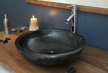 Astuce rénovation de salle de bain : changer le plan vasque. A la place de l'ancienne vasque démodée et souvent âgée, rien de tel qu'une vasque ronde et noire en terrazo bien ancrée dans la modernité. Chic et classe, le duo parfait pour rénover sans faux pas !