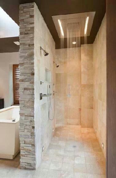Un pommeau jet pluie à LED pour l'espace de la salle de bain dédié à la douche. Aménagée en longueur l'éclairage souligne l'aspect des pierres qui composent ses murs. Elégante et classe, cette douche à l'italienne XXL à tous les atouts pour rendre l'espace douche unique