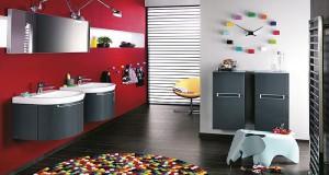 La décoration d'une salle de bain aime la couleur rouge pour son effet dynamisant. Avec un mur rouge, des meubles sous vasque gris anthracte, quelques touches de couleurs flashy ne gâche rien !