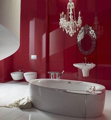 La salle de bain rouge laqué joue avec les éléments du baroque et du moderne. La baignoire blanche aux formes épurées et les vasques suspendues au mur rouge s'allie parfaitement. Un équilibre est instauré.