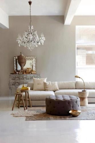 Ce salon au mur principal couleur taupe clair s'harmonise parfaitement avec les nuances claires des alentours. Le canapé lin se démarque du mur tout en conservant la même gamme de nuances. Le pouf taupe foncé quant à lui réchauffe l'ambiance du salon tout entier. Un mariage de teintes élégants et donc réussit !