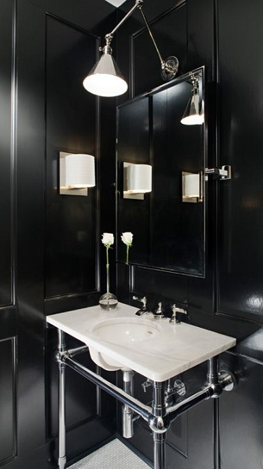 Cette petite salle de bain mise sur le duo noir et blanc pour un effet chic. Loin d'écraser la pièce, les murs noirs font ressortir les éléments qui composent la salle d'eau. Le meuble vasque est d'ailleurs mis en valeur tout comme l'espace disponible en dessous de ce dernier. La lumière tamisée quant à elle se charge d'achever cette déco tendance.