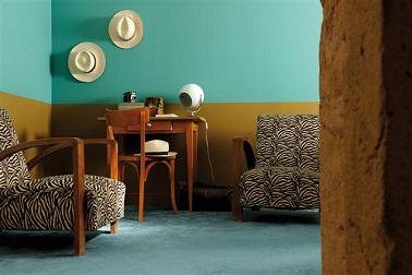 Ambiance rétro tendance dans ce salon avec une peinture ocre posé en soubassement révèle la subtilité du bleu retenu pour peindre le haut des murs. Une association couleurs tendance pour un salon plein de charme. Peinture couleur Malachite et Laiton gamme infiniment Zolpan Ed. 2.