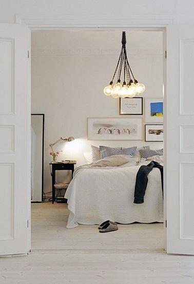 Appel au repos dans cette chambre blanche décorée de lampes de chevet et suspension empruntés au style industriel. Une ambiance de chambre cocooning renforcée par la douceur des tons et matières du linge de lit