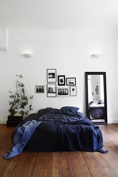 Un lit au centre de la pièce, un mur d'une blancheur immaculée, un miroir posé, quelques cadres et une plante, le décor minimaliste de cette chambre parentale laisse rêveur.