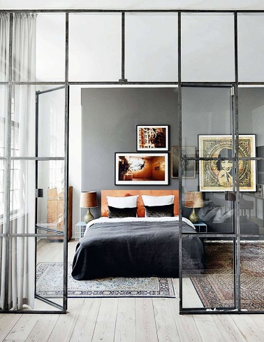 Une verrière design pour fermer cette chambre parentale et une luminosité qui met en valeur tout l'espace, voilà les atouts charme de cette pièce. Affublée d'un parquet en bois très clair d'un mur gris la déco est relevé par des éléments forts mettant en exergue l'ambiance zen. Des tapis qui semblent avoir été chinés dans un autre pays, une parure de lit noire et orange et des cadres invitant au voyage, les accessoires de cette chambre adulte marquent de leur empreinte zen toute l'atmosphère.