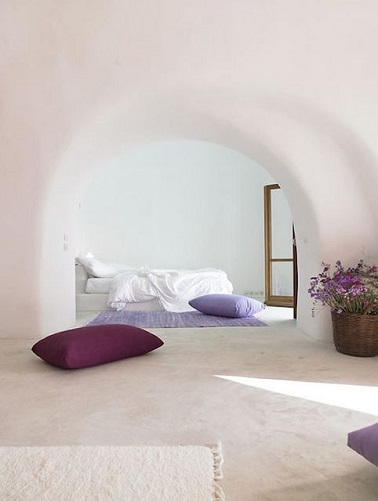 Du blanc et des touches de violet, il n'en faut pas plus pour faire de cette chambre un endroit exquis. Derrière deux arches de style méditerranéen, le lit à fleur de sol s'entoure de tapis et coussins pour le confort et le plaisir des yeux