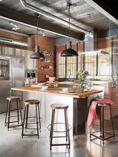Une ambiance loft new-yorkais s'invite dans cette cuisine ! Le style industriel est apporté par les accessoires en métal tels que les tabourets et les deux suspensions vintage. Le plan de travail de l'îlot en bois clair réchauffe la pièce tandis qu'au plafond les poutres et tuyauteries acier ancrent encore plus cette cuisine dans le style indus'. La modernité n'est pas pour autant mise de côté, elle est d'ailleurs relevé par l'inox qui compose à la fois le corps de l'îlot de cuisine, la hotte et le coin réfrigérateur.