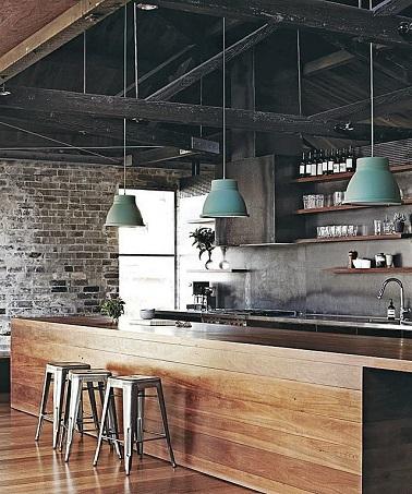 Le bois s'étend dans cette cuisine à la déco indus' discrète. Le mur en briques contraste avec la structure du plafond en acier noir. Les quelques accessoires se chargent d'accentuer le design usine. Les tabourets Tolix en métal amènent la touche vintage tandis que la note de couleur est apportée par les suspensions bleu gris.