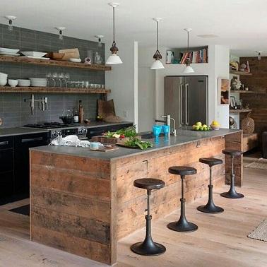 Un esprit industriel brocanté règne dans cette cuisine. Le plan de travail en acier se conjugue à merveille avec la structure en bois brut et les tabourets en métal. Du côté des fourneaux, la crédence en carrelage gris et les meubles noirs apportent la touche industrielle moderne.
