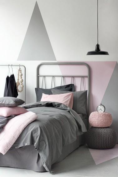 Un lit en métal, et du graphisme gris et rose sur les murs et la