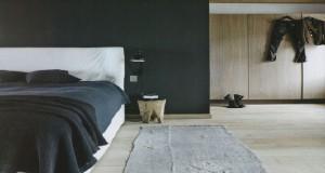 Véritable suite parentale une chambre adulte installée sous les combles qui offrent une déco résolument zen avec la sobriété de la couleur noir en complément des éléments bois que composent les poutres et les grands panneaux de bois en teck clair recouvrant les murs