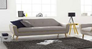 Un canapé en tissu gris perle aux lignes sobres bordé d'un liseré jaune tendre qui s'intègre parfaitement dans une décoration de salon design