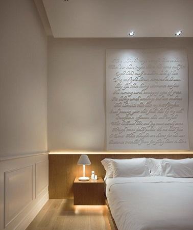 Comme dans une chambre d'hôtel chic, rien ne dépasse dans autour du li de cette luxueuse chambre blanche qui tire son originalité de la tête de lit réalisée avec une typographie en relief sur un châssis de toile blanchie.