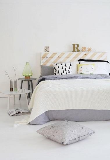 Une chambre joyeuse en blanc et touche de gris ! Tabouret et table basse sont détournés en table de chevet et la tête de lit palette se fait originale avec ses rayures de peinture blanche et jaune