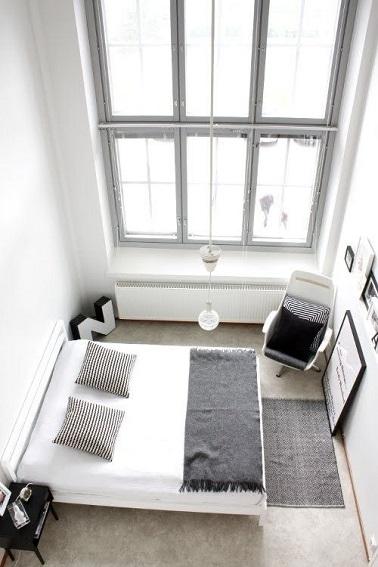 Le minimalisme joue avec le noir et blanc dans cette chambre. Exploitant l'ensoleillement maxi, priorité est donnée aux meubles et éléments de déco au sol pour mettre en avant la belle hauteur sous plafond