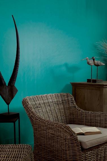Une peinture bleu turquoise dans un salon avec des meubles en osier et bois, c'est la subtilité qu'apporte la teinte Curaçao de Flamant-Tollens. La clarté de cette couleur sur les murs emporte le salon vers les chaudes îles du pacifique.