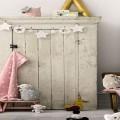 La chambre d'un bébé fille tendance c'est fait de couleurs tendres tel un gris perle, de touches de rose, de meubles en bois clair et d'accessoires de décoration faits maison : guirlandes, penderie, étagères originales…