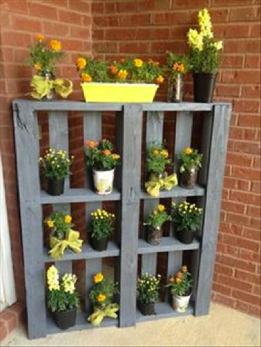 Une palette bois passée à la lasure colorée et appuyée au mur de la maison, du cabanon de jardin ou encore de la clôture et voilà une étagère sympa pour présenter joliment ses pots de fleurs dans le jardin.