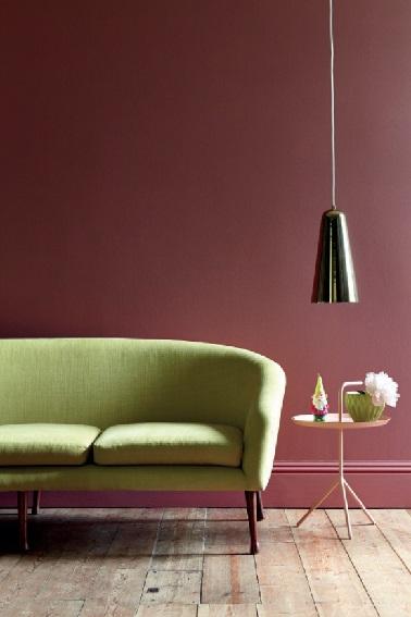 Marier un peinture rouge brun dans le salon avec un canapé vert, une ambiance couleur qu'il faut oser car le rendu final est sublime ! Ajouter un touche de rose avec une petite table, et la déco du salon s'enveloppe d'un brin de féminité.  Peinture couleur Ashes of Roses  et vert Citrine Little Greene .