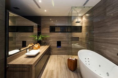 Elégante salle de bain revêtue de bois sur tous ses murs, le sol et le plan vasques qui donne une place de choix à la grande baignoire balnéo et à sa douche italienne fermée de 3 parois de verre.