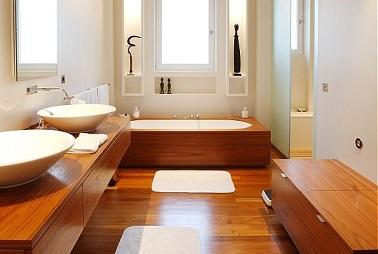 Aménagement luxueux dans une salle de bain avec du chêne doré pour le sol le plan vasque et l'habillage de la baignoire mettant une focal sur les 2 grandes vasques blanches.