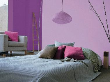Une chambre mariant du violet et un mur parme qui assume son côté féminin. L'ambiance déco de la chambre est rehaussée par une suspension boule et des éléments boisés.