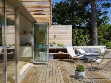 Sur une terrasse qui marie sol et auvent en bois, le baies vitrées et le salon de jardin en acier gris apportent une touche de modernité en complète harmonie