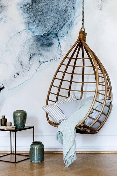 Se lover dans un cocon n'est plus une simple expression avec ce fauteuil suspendu en rotin. En forme d'œuf, ce fauteuil est la définition même du mot détente. Aussi bien adapté pour être disposé à l'intérieur qu'à l'extérieur à condition d'avoir un assez grand espace, ce cocon en rotin permet de revisiter l'usage de ce bois exotique l'utilisant dans une toute nouvelle architecture plus moderne. Agrémenté en son cœur par quelques coussins et une couverture bleu clair, ce fauteuil Broste Copenhagen se tient prêt à vous accueillir dans une ambiance scandinave détente.