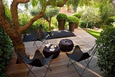 Sur cette terrasse pleine de charme le bois est omniprésent sur deux niveaux dominant un parc à l'allure de jardin zen. Le mobilier noir renforce l'impression de modernité