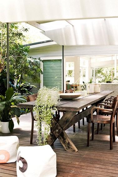 Le style vintage investit la terrasse en bois d'une maison de campagne. Au sol, de fines lames en teck accueillent une table en bois brut protégée du soleil par une voile d'ombrage.