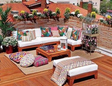Sur le toit, cette terrasse en bois promet un dépaysement absolu dans un décor coloré agrémenté de plantes fleuries. Les coussins du canapé donnent un accent tropical à cette terrasse en lames de Sucupira.