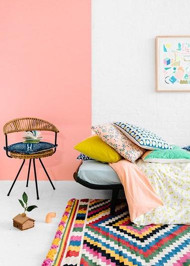 Cette chambre de jeune fille porte haut la couleur rose dans la déco. La peinture rose saumon sur une partie du mur blanc éveille le côté nature ethnique tendance