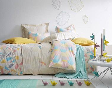 Un linge de lit tout en douceur se dessine dans le graphisme de cette parure de lit en coton aux motifs en forme d'origami assorti de coussins jaune donne du relief à la déco et poétise la pièce. Origami chez Essix