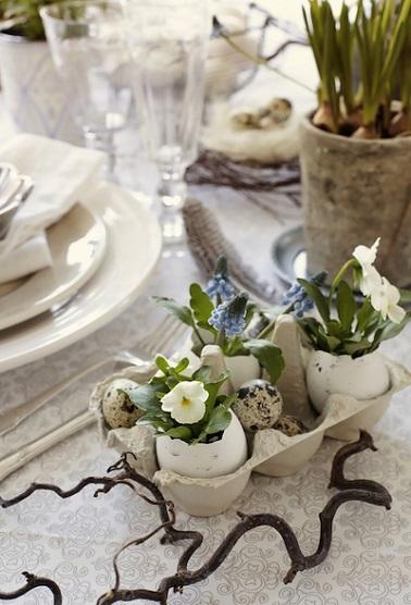 Donner une deuxième vie à vos boîtes d'œufs vides grâce à cette astuce déco ! Pour réaliser cet accessoire déco original, munissez-vous d'une boîte d'œuf en carton et servez vous de coquilles d'œufs décalottées comme des petits vases dans lesquels seront disposés de petites fleurs délicates. Gardez des emplacements de libre pour y disposer quelques œufs de caille cuits durs discrets et mignons pour achever cette déco faite maison simple et tendance à souhait ! Source : benita-le-blog-deco.blogspot.fr