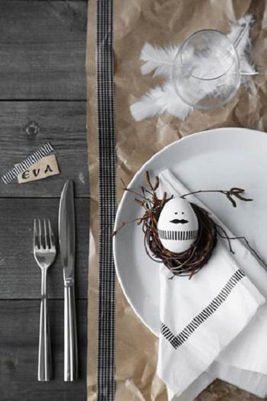 La déco de Pâques ne répond à aucune règle. Alors si votre préférence ne va pas à la couleur, vous pouvez très bien opter pour une déco plus en retenue et sobre. Cette table en est la preuve avec son style rustique sans couleur si chic. Pour contraster avec le bois gris et brut de la table, un chemin de table marron clair vient apporter un peu de luminosité et de relief à cette déco de Pâques très épurée. De jolies plumes blanches et légères viennent d'ailleurs soutenir le verre à pied pour donner un côté aérien à la table. Et pour apporter de la modernité, cette déco adopte des serviettes imprimés avec des rayures noires qui se marient élégamment avec celles qui ornent l'œuf peint posé dans l'assiette qui arbore une moustache tendance. L'originalité en subtilité, un atout charme pour réaliser sa déco de Pâques sans en faire trop ! Source photo : pinterest / inspidiy.fr