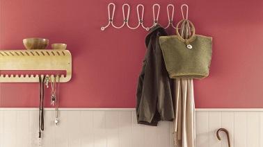 La peinture couleur rose se montre dès l'entrée grâce à cette teinte rose foncé. Le soubassement en bois blanc éclaire cette entrée chaleureuse. Dulux Valentine