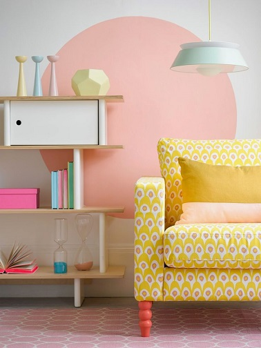 Peindre un rond rose sur le mur blanc du salon avec un canapé jaune, c'est parfait pour colorer les humeurs en pastel !
