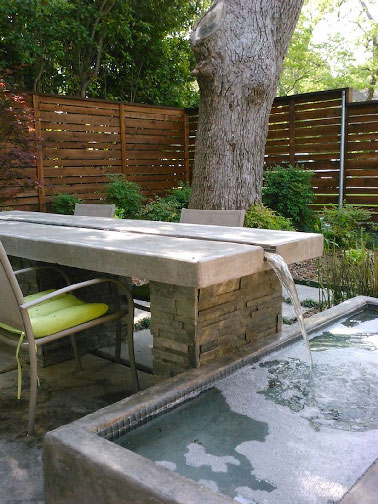 table de jardin avec coul e d 39 eau tombant dans un bassin. Black Bedroom Furniture Sets. Home Design Ideas