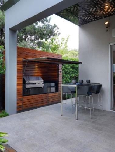 Installée à côté de la terrasse, un concept de cuisine extérieur original avec un barbecue installé dans une cabane en teck