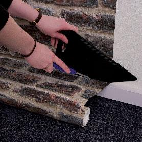 Après avoir posé le papier peint sur le mur, faire la découpe au bas du mur à l'aide  d'une règle et d'un cutter