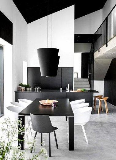 Une cuisine ouverte dans une maison d'architecte qui structure son espace ouvert sur le séjour par un jeu de noir et blanc avec la peinture et les meubles design