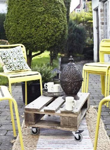 Une table basse fabriquée avec une palette bois coupée en deux, une dimension suffisante pour prendre le thé dans le jardin. Avec des chaises de jardin métallique, le mélange de styles est élégant