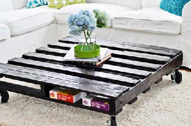 Une table basse palette montée sur roulettes et peinte en noir dans un salon blanc nous on dit oui ! En plus, la palette est bien pratique pour ranger les livres.