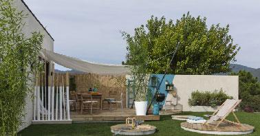 Accolée à la maison, une terrasse en bois montée sur dalle béton et lambourdes. Lames en pin massif rainurée disponible en aspect bois naturel, blanc et beige.