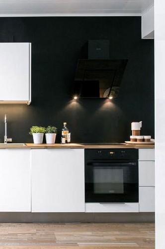 Une déco haute couture en blanc et noir pour une cuisine moderne. Sur le mur de la crédence une peinture noir satin sublime la zone cuisson de cette cuisine blanche sans nuire à sa luminosité. Agrémentée de  2 ou 3 spots le mur noir révèle son élégance.