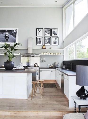Une cuisine design qui fait rêver par sa surface ouverte sur salon. Aux meubles laqués blanc est associé une peinture d'un gris si clair qu'il en paraît presque blanc. Avec le noir des plans de travail et la hotte inox, l'ensemble ouvre des perspectives de partages dans une cuisine hors du commun.
